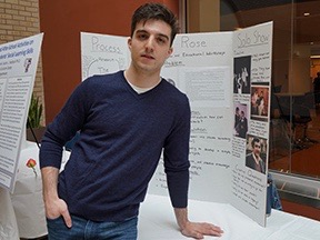 A boy wearing a dark navy polo stands in front of a poster board.