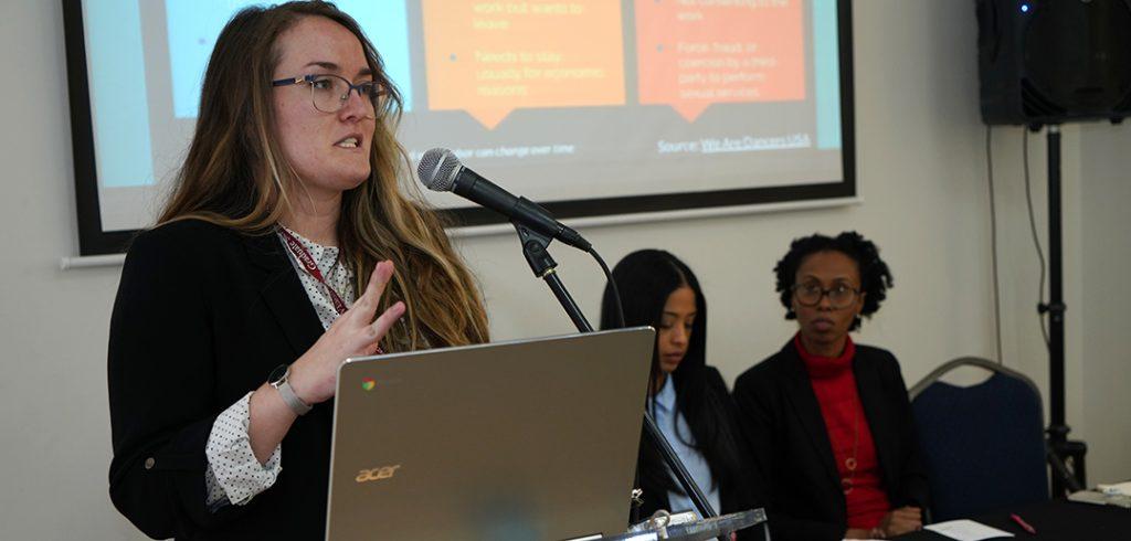 Abigail Asper presents at podium.