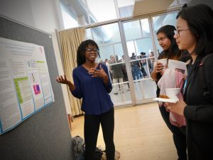 Itunu Ademoyo gestures toward her poster as students look on.
