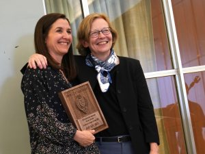 Dean Mast stands next to Amy Roy, who holds a plaque.