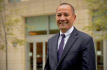 Dean Cruz stands in front of a building on the Lincoln Center campus.