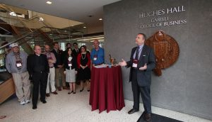 Jack Kawa addresses a group in front of the Hughes Hall signage on the ground floor of Hughes Hall.