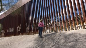 A person looks at a barrier seperating Mexico from the United States