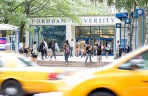People walk in front of the entrance to Fordham's Lowenstein Center, as two yellow cabs pass in the foreground.