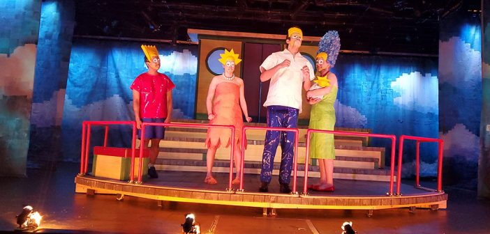 The cast of Mr. Burns dressed as Bart, Lisa, Homer and Marge, on stage in Pope Auditorium.