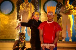Actors portraying Mr. Burns and Bart Simpson stand on stage at Pope Auditorium.
