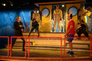 Actors portraying Mr. Burns and Bart Simpson fight with swords in Pope Auditorium.