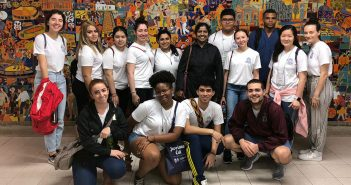 Fordham pre-health students in Cali, Columbia for a service learning trip. They are standing against a colorful mosaic.