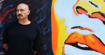 Portrait of Fordham grad Steve Romagnoli standing in front of a graffiti mural near his home in Bushwick, Brooklyn
