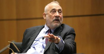 Joseph Stiglitz gestures with his right hand while sitting on stage at the McNally Amphitheatre at Fordham's Lincoln Center campus.
