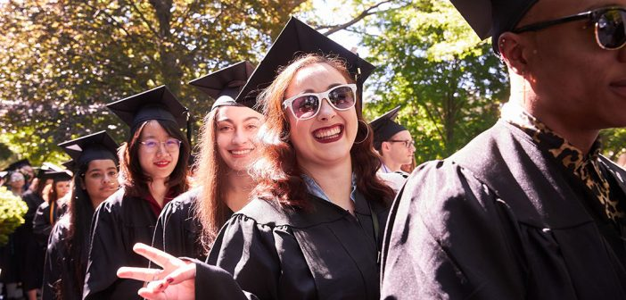 Line of graduates wearing black academic gowns, including a woman with white sunglasses