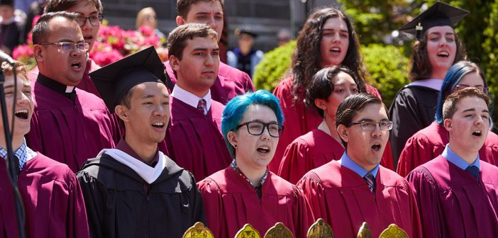 Choir members dressed in red, including one with blue hair and glasses, sing.