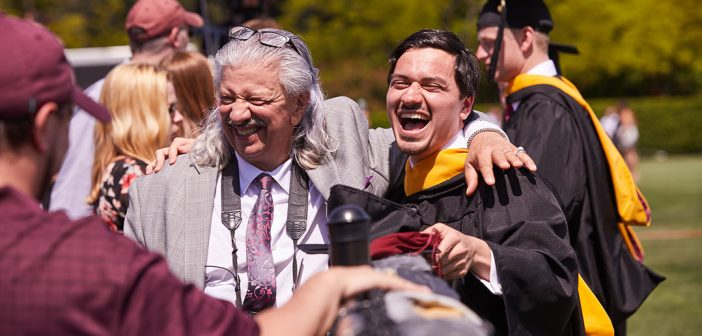 A male graduate laughs as older man in tie puts his arm around his shoulder