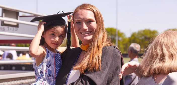 Blond woman holds a child wearing an academic cap