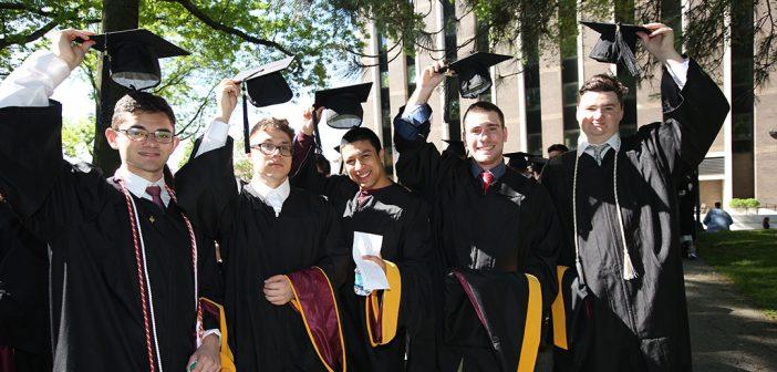 Five graduates raising their black caps