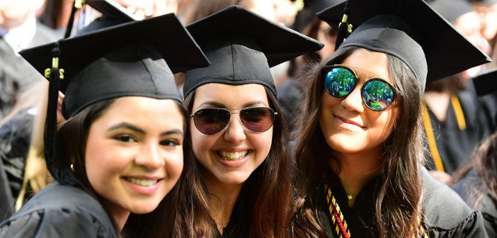 three women with black graduation caps, two in sunglasses