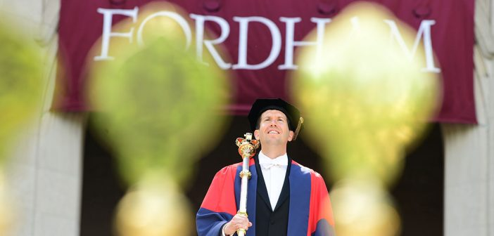 Patrick Hornbeck stands in between two gold staffs topped with medallions, a Fordham banner above his head
