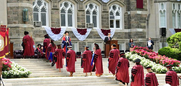 Doctoral students walking up the terrace steps lined with pink and white flowers