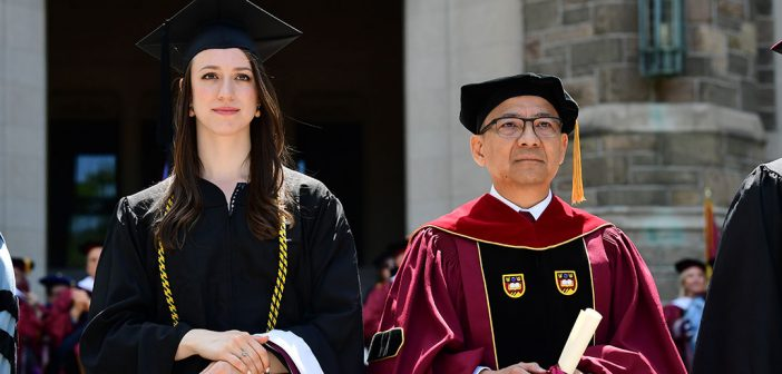 Student in black cap and gown stands on Keating Terrace with Dean Tito Cruz of the Graduate School of Religion and Religious Education