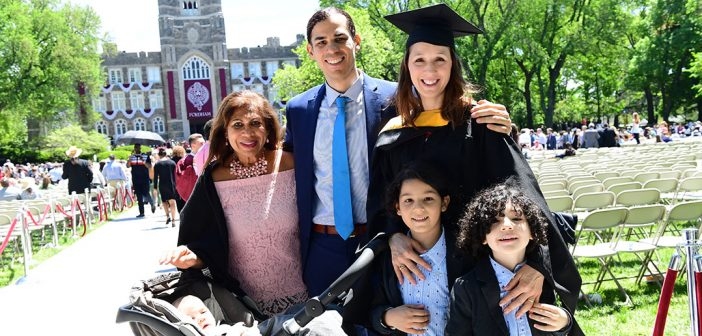 A woman graduate poses with her family on Edwards Parade