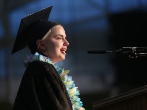 A girl with short blonde hair and a black graduation gown speaks in front of a microphone