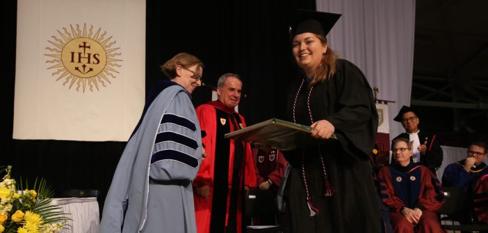 A girl wearing a black graduation gown smiles and receives a plaque from a woman wearing a light blue graduation gown