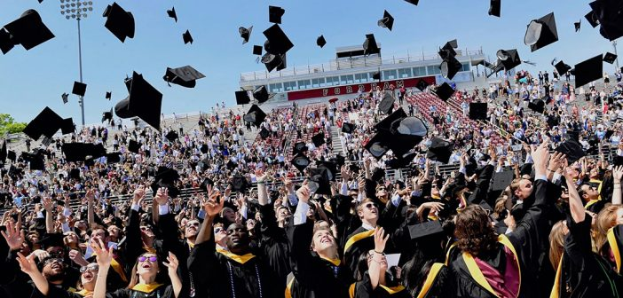 Graduates wearing black academic robes throw their hats in the air on the football field
