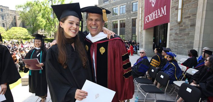 A graduate wearing a black academic robe poses fora picture with Tim Shriver, wearing a red academic gown