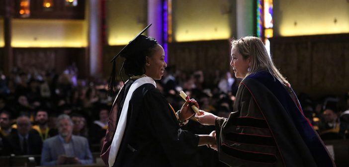 A woman in black academic robes receives a diploma from another woman