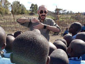A man wearing sunglasses speaks and gestures with his hands in front of a crowd of Kenyan children