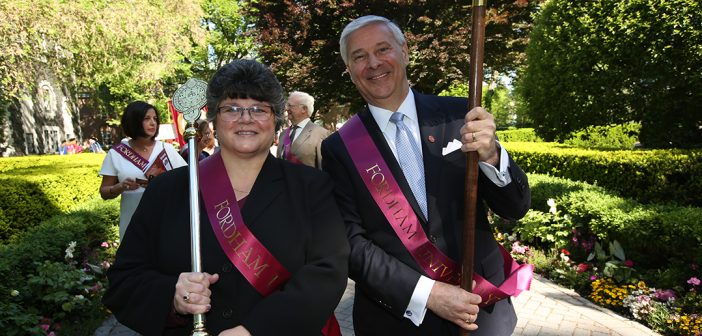 A man and woman wearing dressed in formal clothes sport red sashes