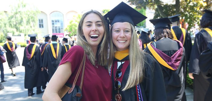 A woman graduate poses for a picture with another woman