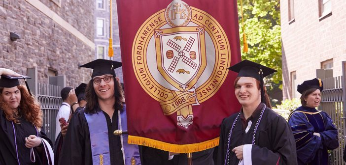 Two graduates pose for a picture with a red and yellow banner