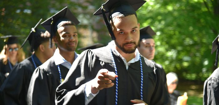 A man in a black cap and gown points at the camera with a half smile.