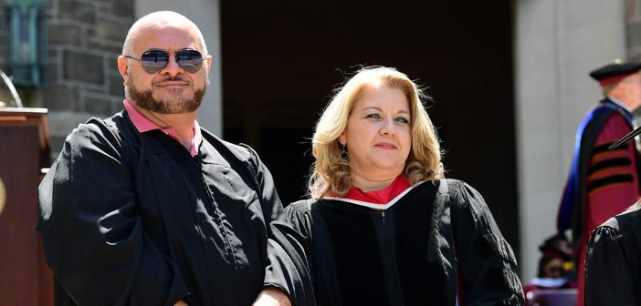A man and woman wearing black academic robes