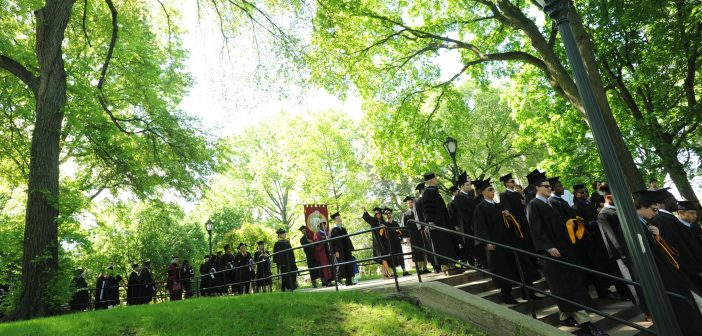 Students wearing black graduation gowns walking in a line in front of a backdrop of green foliage