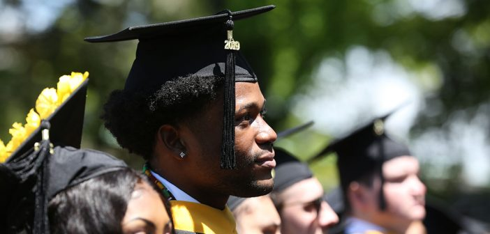 A man wearing an academic cap looks off to the distance