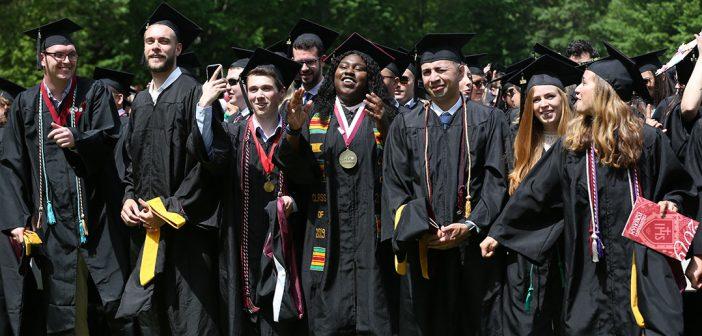 A dozen graduates standing in a line cheer