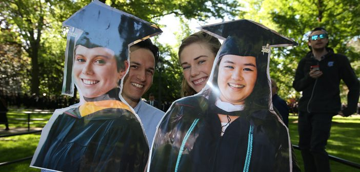 Two people hold up signs with graduates faces on them