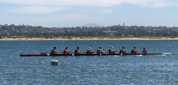 The men's crew team rowing on the water.