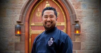 A man wearing a black priest robe smiles in front of a set of church doors