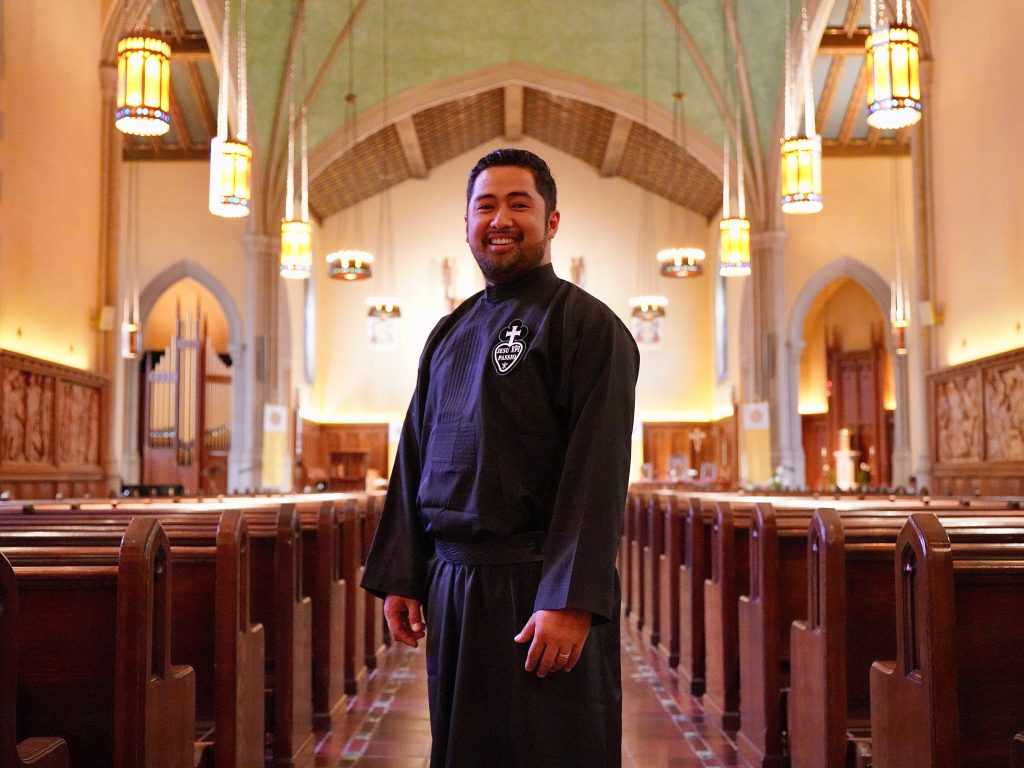 A man wearing black priest robes stands in the middle of the University Church, between the church pews