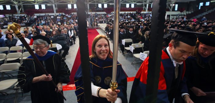 A woman wearing a faculty graduation gown holds a pole