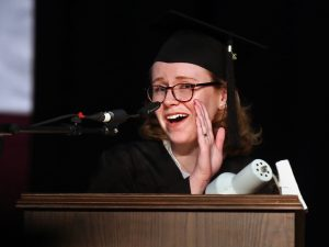 A girl wearing glasses speaks at a podium while holding a hand to the side of her face