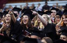 Students wearing black graduation gowns cheer and point their fingers