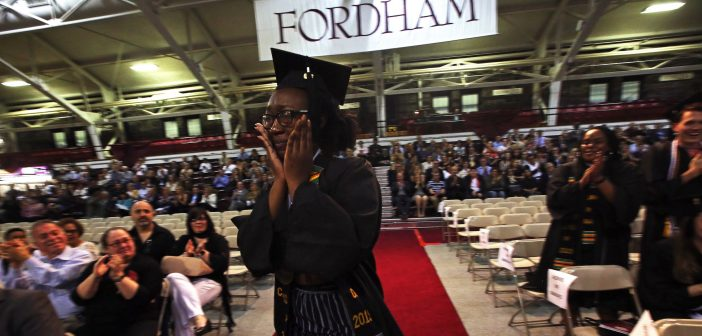 A girl wearing a black graduation gown holds hands to her tear-streaked face and walks along an aisle