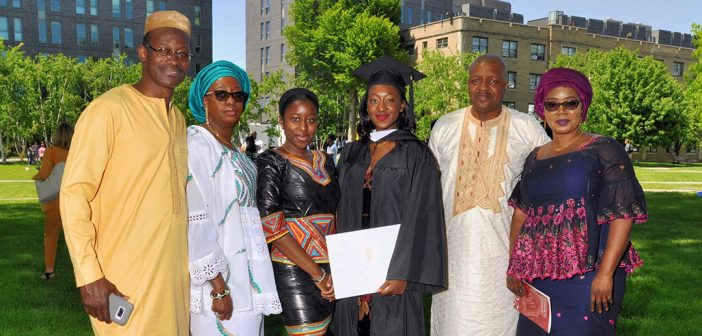 A family poses with a graduate wearing a black academic robe