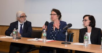 One man and two women panelists at a long table with microphones