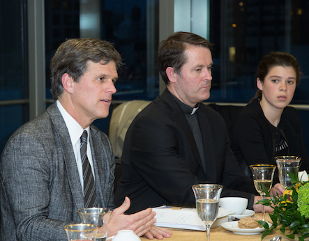 Timothy Shriver in jacket and tie sitting next to Father Mick McCarthy at a luncheon at Fordham in 2016