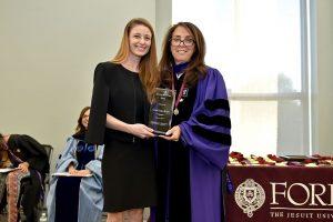 Caroline Dahlgren, wearing a black dress, holds an award with Donna Rapiaccioli, wearing purple
